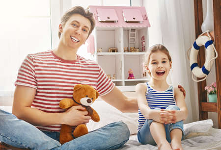 Happy father and daughter girl play with toys at home. Funny lovely family is having fun in kids room.