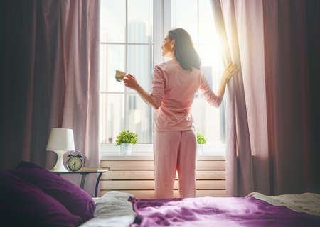 Happy young woman enjoying sunny morning and coffee. Girl drinks cup of tea, hot beverage near window. Stock Photo