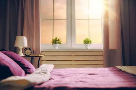 hotel bedroom: Bedroom in purple colors. Big comfortable double bed in elegant classic room.