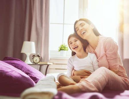 Une belle fille et sa mère aiment le matin ensoleillé. Bon moment à la maison. L'enfant se réveille du sommeil. Famille jouant sur le lit dans la chambre. Banque d'images - 77784725