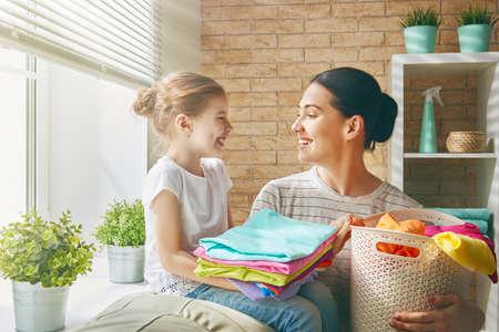 Joven y bella mujer joven y niña poco ayudante se están divirtiendo y sonriendo mientras se hace el lavado de ropa en casa.