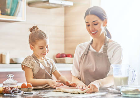 domestic: Happy loving family are preparing bakery together. Mother and child daughter girl are cooking cookies and having fun in the kitchen. Homemade food and little helper.