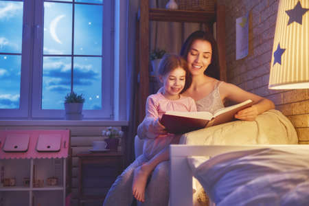 home: Family reading bedtime. Pretty young mother reading a book to her daughter. Happy time at home.