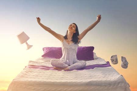 Vrouwen dromen. Mooi meisje vliegt in haar bed door de sterrenhemel.