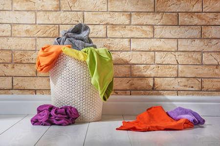 Cesto con biancheria colorata in piedi sul pavimento nella lavanderia. Archivio Fotografico - 78027052