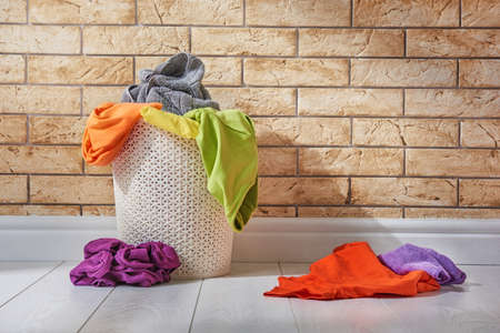 Basket with colored linen standing on the floor in the laundry room.