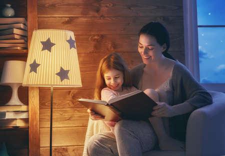 Familie, die Schlafenszeit liest. Hübsche junge Mutter liest ein Buch zu ihrer Tochter. Glückliche Zeit zu Hause. Standard-Bild - 78027790