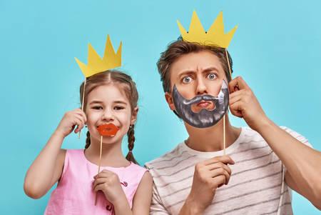 밝은 파란색 벽의 배경에 재미있는 가족. 아버지와 딸이 종이 액세서리와 함께. 아빠와 아이가 지팡이에 종이 왕관을 들고 있습니다.