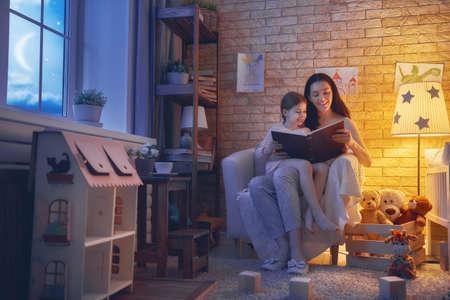 Familie, die Schlafenszeit liest. Hübsche junge Mutter liest ein Buch zu ihrer Tochter. Glückliche Zeit zu Hause. Standard-Bild