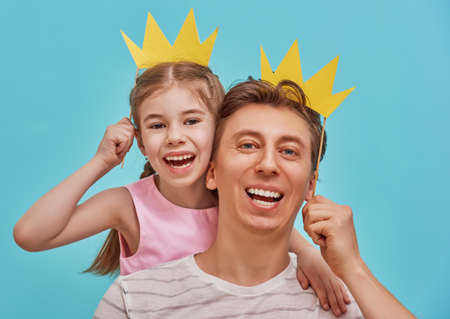 Funny family on a background of bright blue wall. Father and his daughter girl with a paper accessories. Dad and child are holding paper crown on stick.