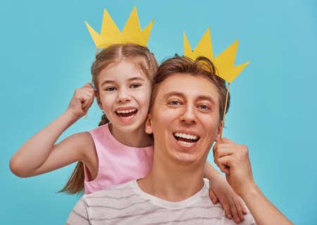 Grappige familie op een achtergrond van heldere blauwe muur. Vader en zijn dochtermeisje met document toebehoren. Vader en kind houden papieren kroon op stok.