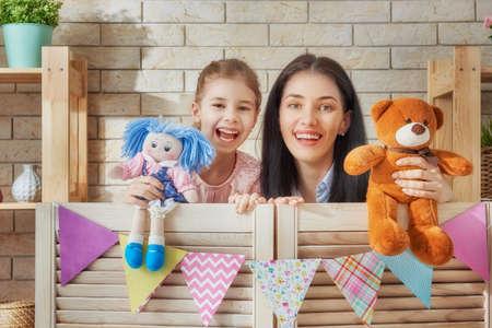 幸せな愛情のある家族。母と子供の部屋で彼女の娘。面白いママと楽しい時を過すと屋内での人形劇のパフォーマンス素敵な子。人形とテディベア 写真素材