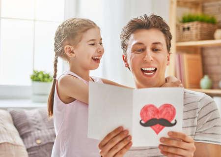幸せな父の日!子娘はお父さんを祝福し、彼にはがきを与えます。パパと女の子笑顔とハグします。家族の休日と一体感。