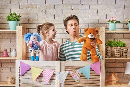 幸せな愛情のある家族。父と娘の子供部屋。面白いお父さんと楽しい時を過すと屋内での人形劇のパフォーマンス素敵な子。人形とテディベア。