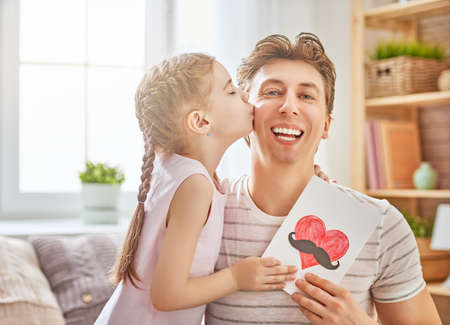 Happy fathers day! Child daughter congratulates dad and gives him postcard. Daddy and girl, kissing, smiling and hugging. Family holiday and togetherness. Stock Photo