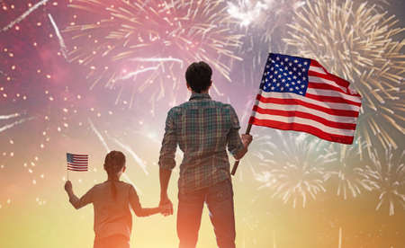 Patriotic holiday. Happy kid, cute little child girl and her father with American flag. USA celebrate 4th of July. 스톡 콘텐츠
