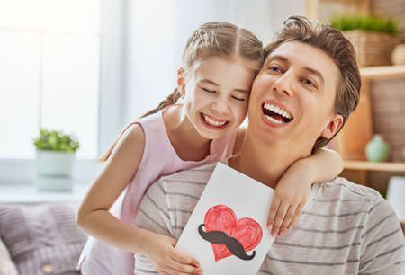 Happy fathers day! Child daughter congratulates dad and gives him postcard. Daddy and girl smiling and hugging. Family holiday and togetherness.