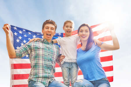 Patriotic holiday. Happy family, parents and daughter child girl with American flag outdoors on blue sky background. USA celebrate 4th of July. Stock fotó