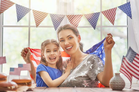 mama e hija: Patriotic holiday. Mother and daughter are doing burgers. Happy family are celebrate 4th of July. Cute little child girl and her mom with American flag in the room at home.