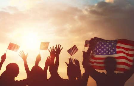 Vacaciones patrióticas. Siluetas de la gente que sostiene la bandera de los EEUU. América celebra el 4 de julio.