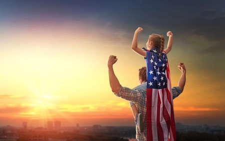 Patriottische vakantie. Gelukkige familie, vader en zijn dochter kind meisje met Amerikaanse vlag buitenshuis op achtergrond zonsondergang cityscape. De VS vieren 4 juli. Stockfoto