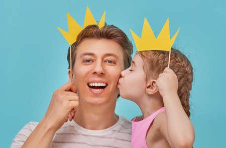 Famiglia divertente su uno sfondo di parete blu brillante. Padre e sua figlia con un accessorio di carta. Papà e figlio stanno tenendo la corona di carta sul bastone. Archivio Fotografico - 78529093