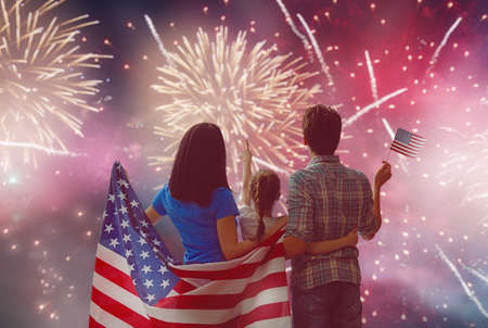 Patriotic holiday. Happy family, parents and daughter child girl with American flag outdoors. USA celebrate 4th of July. 版權商用圖片 - 78504506