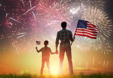 Patriotic holiday. Happy kid, cute little child girl and her father with American flag. USA celebrate 4th of July. 版權商用圖片 - 78504509