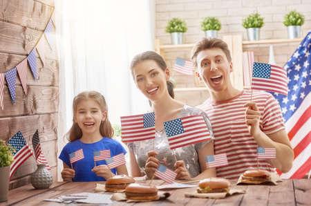 애국적인 휴일. 어머니, 아버지와 딸이 햄버거를하고 있습니다. 행복한 가족은 7 월 4 일을 축하합니다. 집에서 방에 미국 국기와 함께 귀여운 작은 아