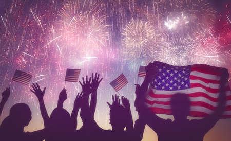 julio: Vacaciones patrióticas. Siluetas de la gente que sostiene la bandera de los EEUU. América celebra el 4 de julio.