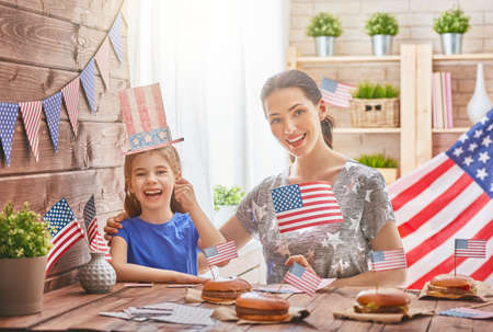 Patriotic holiday. Mother and daughter are doing burgers. Happy family are celebrate 4th of July. Cute little child girl and her mom with American flag in the room at home.