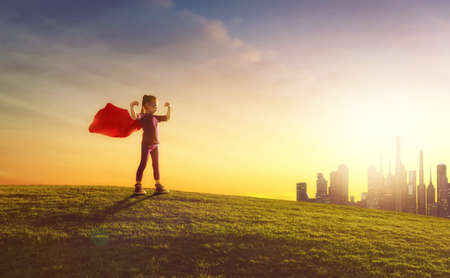 Petite fille de l'enfant joue super-héros. Enfant sur le fond de coucher de soleil ciel. Concept Girl power Banque d'images