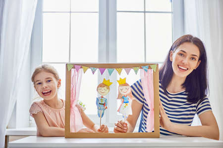 Happy loving family. Mother and her daughter in kids room. Funny mom and lovely child having fun and playing performance in the puppet theater indoors. Prince and princess. Standard-Bild