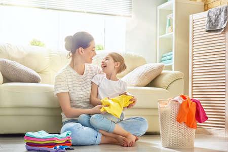 Mooie jonge vrouw en kindermeisje kleine helper hebben plezier en lachen terwijl ze thuis wassen.