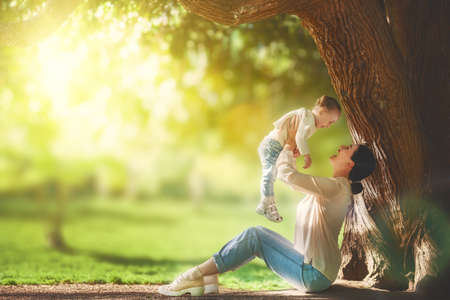 pretty baby: Mother and daughter sitting under the tree on summer lawn. Happy family playing outdoors. Pretty young mom having fun with her baby in the park outside. Stock Photo