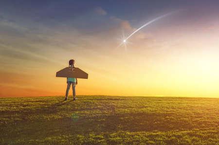少女は、宇宙飛行士を果たしています。夕焼け空の背景の子。子供は流れ星を見て、宇宙飛行士になることを夢見てします。