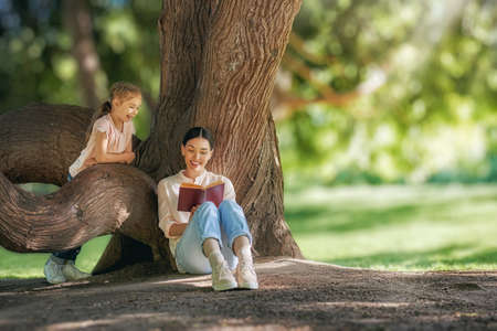 Mother and daughter sitting under the tree on summer lawn. Happy family playing outdoors. Pretty young mom reading a book to her child in the park outside.