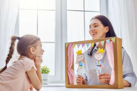 Happy loving family. Mother and her daughter in kids room. Funny mom and lovely child having fun and playing performance in the puppet theater indoors. Prince and princess. Archivio Fotografico