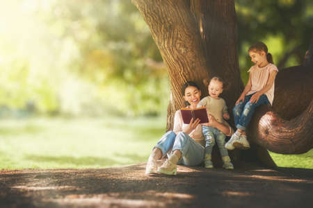 Mother and daughters sitting under the tree on summer lawn. Happy family playing outdoors. Pretty young mom reading a book to her children in the park outside. Stock Photo