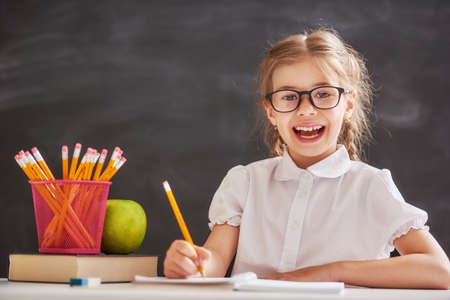 Back to school! Happy cute industrious child is sitting at a desk indoors. Kid is learning in class on background of blackboard.