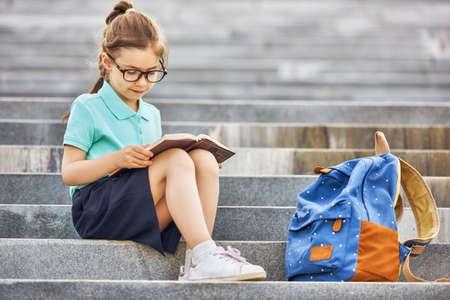 Aluno da escola primária com livro na mão. Menina com mochila perto de construção ao ar livre. Início das aulas. Primeiro dia de outono.