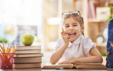 新学期!幸せなかわいい勤勉な子は室内で机に座っています。子供はクラスで学んでいます。 写真素材