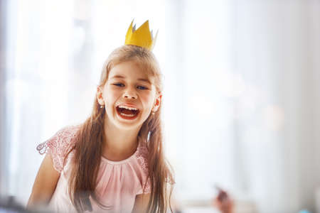 Cute little girl in a princess costume. Pretty child preparing for a party. Beautiful queen in gold crown. Stock Photo