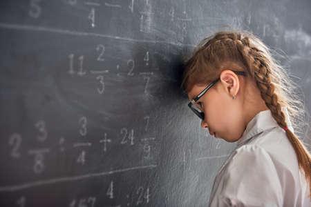 Trudny dzień w szkole! Smutny dziecko blisko blackboard indoors. Dziecko uczy się w klasie. Złożona matematyka, arytmetyka i przykłady. Liczby napisane kredą na pokładzie. Zdjęcie Seryjne