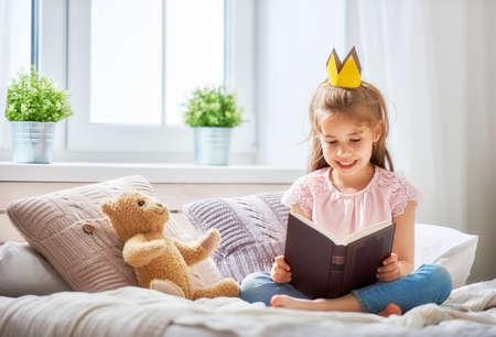 귀여운 작은 아이 소녀 침실에서 책을 읽고. 창 근처 침대에 앉아 크라운와 아이.