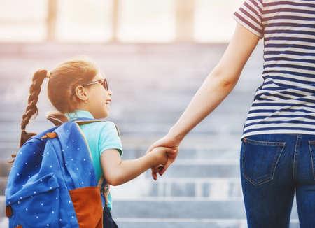 O pai e o aluno da escola primária andam de mãos dadas. Mulher e menina com mochila nas costas. Início das aulas Primeiro dia de outono.