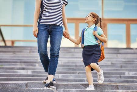 Rodzice i uczniowie szkoły podstawowej idą w parze. Kobieta i dziewczyna z plecakiem za plecami. Początek lekcji. Pierwszy dzień upadku.