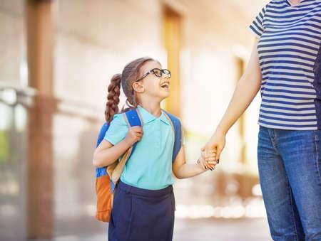 niños saliendo de la escuela: Padres y alumnos de la escuela primaria van de la mano. Mujer y muchacha con el morral detrás de la parte posterior. Comienzo de lecciones. Primer día de otoño.
