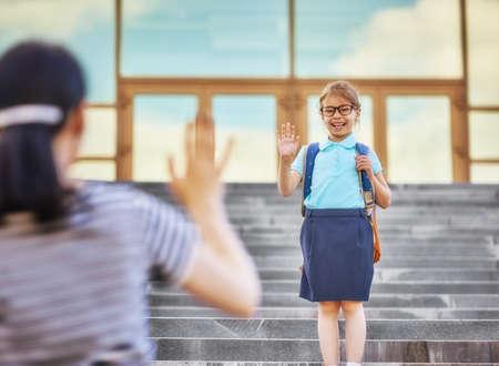 Ouders en leerlingen van de basisschool gaan hand in hand. Vrouw en meisje met rugzak achter de rug. Begin van lessen. Eerste dag van de herfst.