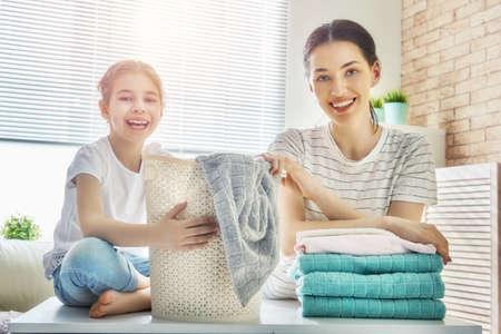 美しい若い女性と子供の女の子小さなヘルパーを楽しんで、家で洗濯しながら笑みを浮かべてします。